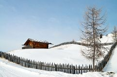 Old winter cottage with fence Stock Photography