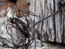 Old wire attached to stone and wood wall wrapping rock stock photography
