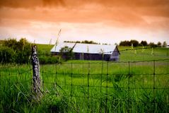 Old Wire Fence and Barn. An old, rotting wire fence stands in the foreground with an old barn in the background, under a stormy, orange sky stock photo