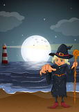 An old witch holding a stick at the beach Royalty Free Stock Photo