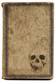 Old witchcraft  book. Very old brown book with framed cover with a stamped skull with plenty space for title such as witchcraft, etc... Good image for halloween Royalty Free Stock Photos