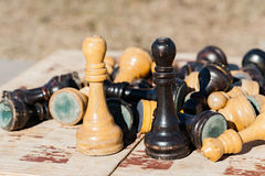 Old and withered chess kings stand face to face on an old chess. Board. Other chess pieces lay in pile behind of them. The game ended up in a bad way. Talk Royalty Free Stock Photos