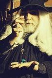 Old wizard pendant for hypnosis. Old man wizard with long gray hair beard in black costume and hat for Halloween holding blue gem stone and silver pendant for stock photos