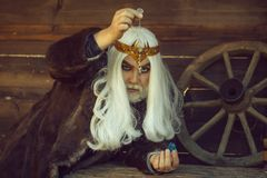 Old wizard with stone and pendant for hypnosis. Old bearded man wizard in golden crown with long white hair and beard holding blue gem stone and silver pendant stock photography