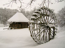 Old wodden contry house and water mill. Pictured in winter in Astra traditional civilisation open-air museum in Sibiu, Romania Stock Photo