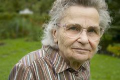 Old woman. Outdoors on the background of the green trees Royalty Free Stock Image