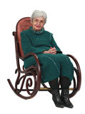 Old woman. Sitting on a wooden rocking chair isolated against a white background Royalty Free Stock Images