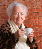 Old woman. Enjoying coffee or tea cup over brick background Stock Photo