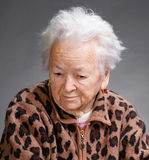 Old woman. Old sad woman on a gray background royalty free stock image