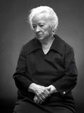 Old woman. B&W portrait of sad old woman on a gray background royalty free stock photos