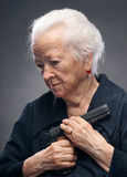 Old woman. With pistol on a gray background royalty free stock photography