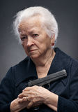 Old woman. Close-up portrait of old woman with pistol on a gray background royalty free stock photos