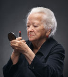 Old woman. Closeup portrait of old woman with lipstick and mirror on a gray background stock photos