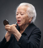 Old woman. Closeup portrait of old woman with lipstick and mirror on a gray background stock photography
