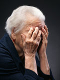 Old woman. Unhappy old senior woman with hands to her face on a gray background stock photos