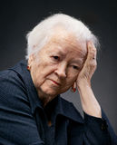 Old woman. Portrait of a thoughtful senior woman with hand on forehead on gray background stock photos