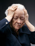 Old woman. Portrait of a sad old woman holding her head isolated against gray royalty free stock photos