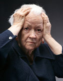 Old woman. Portrait of a sad old woman holding her head isolated against gray royalty free stock photo