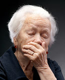 Old woman. Unhappy old senior woman with hands to her face on a gray background stock photography