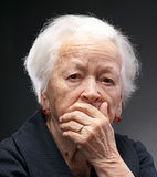 Old woman. Old sad woman with hand on her face on a gray background stock photos
