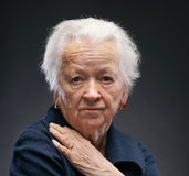 Old woman. On a gray background stock photography