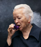 Old woman. Senior woman with asthma inhaler on gray background Royalty Free Stock Image