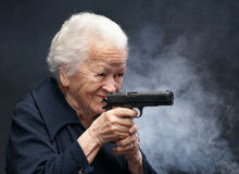 Old woman. With pistol in smoke on a gray background royalty free stock image