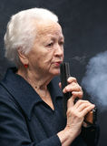 Old woman. Blows a smoke from a pistol on a gray background Stock Image