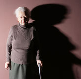 Old woman. With a cane on brown background royalty free stock images
