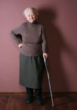 Old woman. With a cane on brown background royalty free stock photo