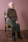 Old woman. Sitting on a chair with a cane on brown background royalty free stock photography