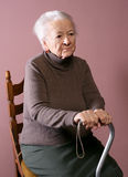 Old woman. Sitting on a chair with a cane on brown background royalty free stock photo