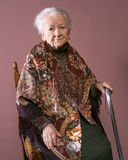 Old woman. Sitting on a chair with a cane on brown background stock image