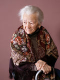 Old woman. With a cane on brown background stock photos