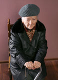 Old woman. Sitting on a chair with a cane on brown background stock photography