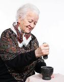 Old woman. Preparing the spices in a mortar on a white background Stock Photos