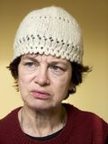 Old Woman. Woman wearing winter hat. Many wrinkles on her face. Old woman sad expression on face royalty free stock photography