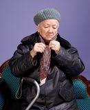 Old woman adjusting her scarf. On a lilac background Royalty Free Stock Photo