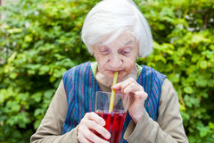 Old woman with alzheimer disease drinking raspberry juice Royalty Free Stock Photo