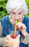 Old woman with alzheimer disease drinking raspberry juice Stock Image