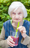 Old woman with alzheimer disease drinking raspberry juice Royalty Free Stock Images