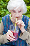 Old woman with alzheimer disease drinking raspberry juice Royalty Free Stock Photos