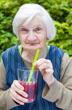 Old woman with alzheimer disease drinking raspberry juice Stock Photography