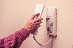 Old woman answering intercom Royalty Free Stock Photography
