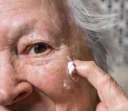 Old woman applying anti-aging cream Royalty Free Stock Photos
