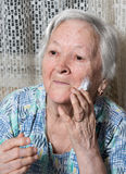 Old woman applying anti-aging cream. At home Stock Photo