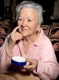 Old woman applying anti-aging cream Royalty Free Stock Image
