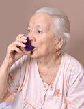 Old woman with asthma inhaler Royalty Free Stock Photo
