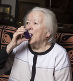 Old woman with asthma inhaler Stock Images