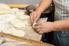 Old woman baking pies in her home kitchen. Grandma cooks pies. Home cooked food. omemade mold cakes of the dough in the ederly wom. En`s hands. The process of Stock Images